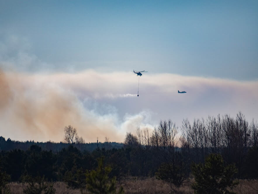 Descripción: Helicopters and planes deployed to drop water on the blaze
